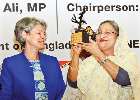 """Prime Minister Sheikh Hasina receiving a special memento titled """"Tree of Peace"""" from UNESCO Director General Irina Bokova in recognition to her outstanding contribution to the promotion of girls' and women's education at Bangabandhu International Conference Centre in the capital on the occasion of the International Literacy Day 2014 on Monday.photo: PID"""