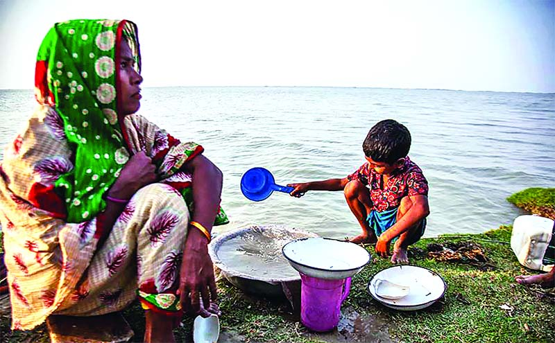 A mother and child separating salt from water at Gabura village in Khulna recently. Sea-water intrusion is increasing salinity in the drinking water reservoirs in Sundarban coastal area.	photo: Observer