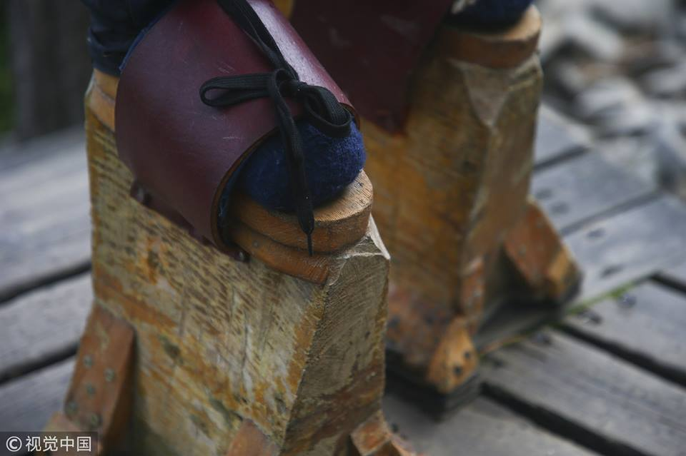 Man makes huge wooden shoes for weight training