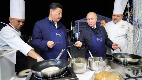 Xi Jinping and Vladimir Putin cook pancakes while visiting 'The Far East Street' exhibition on the sidelines of the Eastern Economic Forum in Vladivostok on Tuesday. (AFP)