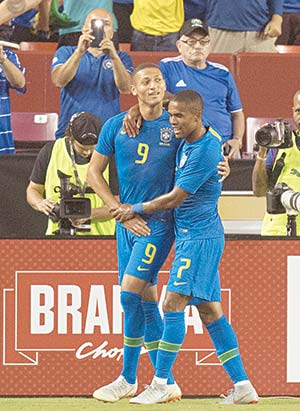 Brazil's Richarlison (C) celebrates his goal with teammate Douglas Costa (R) against El Salvador during an international friendly at FedEx Field in Landover, MD, on September 11, 2018.	photo: AFP