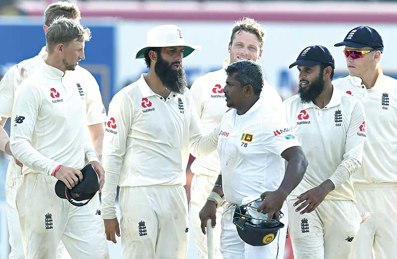 Sri Lanka's Rangana Herath (3R) walks off the field with England cricket team members after England won the opening Test cricket match against Sri Lanka at the Galle International Cricket Stadium in Galle on Friday. photo: AFP