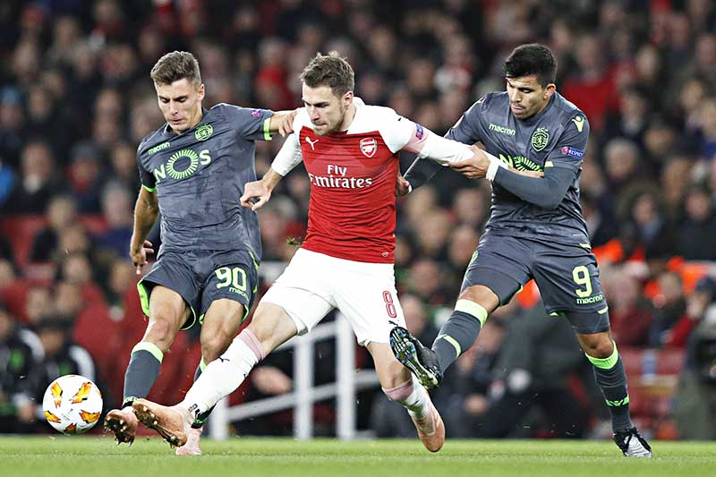 Arsenal's Welsh midfielder Aaron Ramsey (C) holds off Sporting's Argentinian forward Marcos Acuna (R) during their UEFA Europa league group stage football match between Arsenal and Sporting Lisbon at the Emirates stadium in London on November 8, 2018. 	photo: AFP