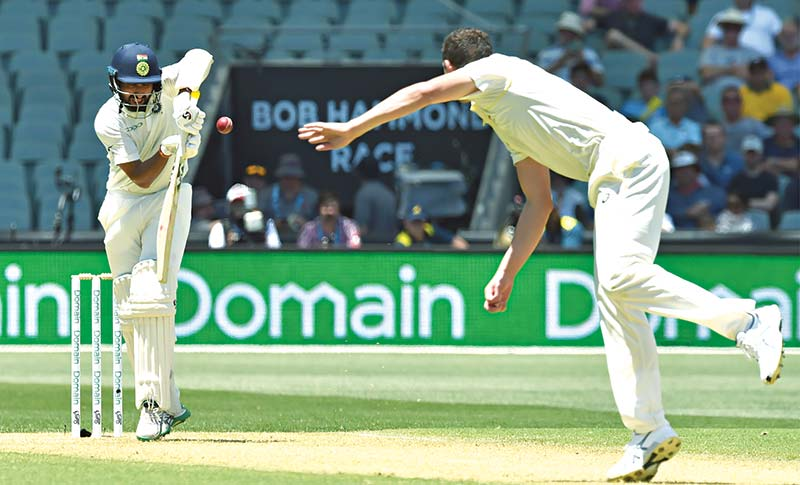 India's batsman Cheteshwar Pujara (L) plays a shot off Australia's paceman Josh Hazlewood (R) during day one of the first cricket Test match at the Adelaide Oval on Thursday. 	photo: AFP