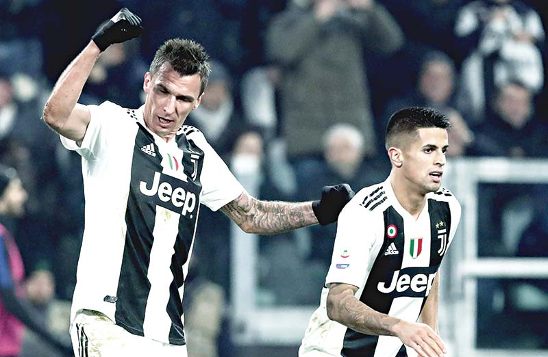 Juventus' Croatian forward Mario Mandzukic (L) celebrates with Juventus' Portuguese defender Joao Cancelo after scoring during the Serie A football match Juventus vs InterMilan at the Stadio delle Alpi in Turin on Friday.	photo: AFP