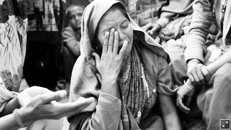 A relative of Yogesh Raj, a Hindu activist, cries after Raj got arrested for leading the protests in which two people died on Monday, in Nayabans village in Bulandshahr district, Uttar Pradesh, India.	photo : reuters
