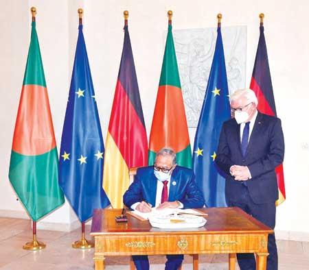 President Mohammad Abdul Hamid puts his signature on the visitors' book